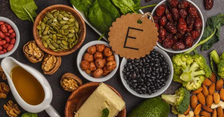 boluri cu alimente bogate in vitamina e pe masa: nuci, avocado, migdale, seminte dovleac, kale