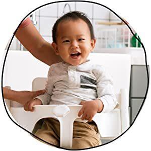 copil asezat de mama in scaun cu masuta pentru a manca